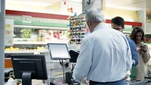 Kassierer und Käufer an der Kasse im Supermarkt