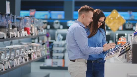 Thumbnail for Happy Family Couple Man and Woman Standing at the Counter with Mobile Phones in Casual Clothes