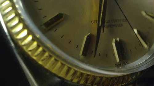 Macro of watch as second hand ticks past minute and hour hands