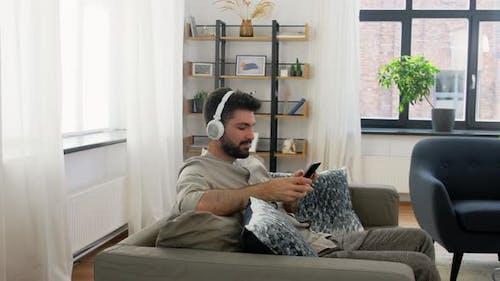 Man in Headphones Listening To Music on Smartphone