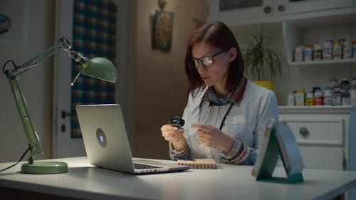 Working from home 30s female doctor shows online patient how to use pulse oximeter