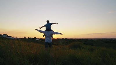 Dad and Son Playing in Meadow at Sunset