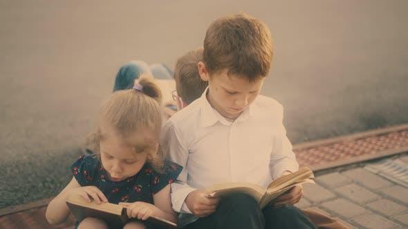 Serious Children Read Textbooks Sitting on Grey Pavement