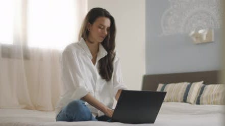 Thumbnail for A woman in white shirt working on a computer, while sitting in bed