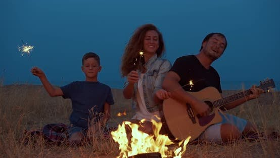 Thumbnail for Happy Family of Campers Around Burning Bonfire Holding Sparkler, And Smiling Tourism Leisure