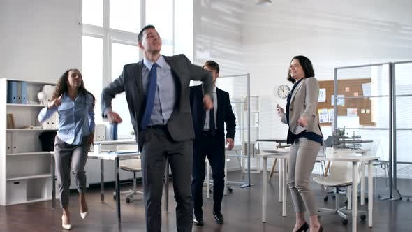 Cover Image for Businessman Dancing Energetically with Team of Coworkers