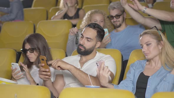 Thumbnail for Relaxed Men and Women of Different Ethnicities Sitting with Smartphones in Cinema. Group of People