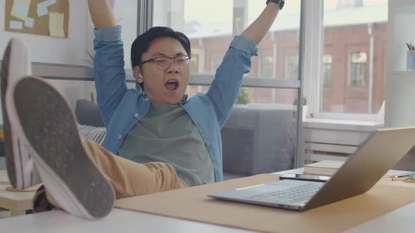 Thumbnail for Sleepy Asian Office Worker Sitting with Feet on Desk and Yawning