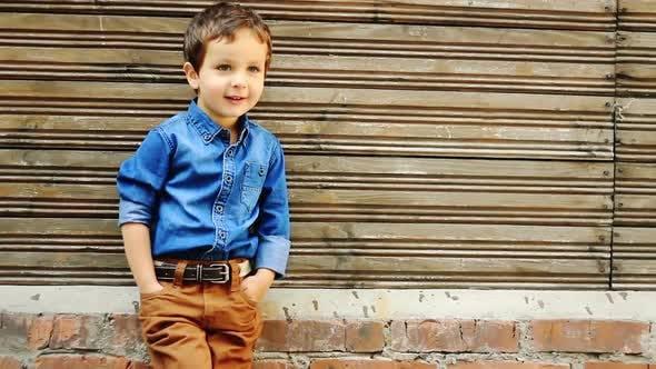 Netter dreijähriger Junge posiert gegen hölzerne Hauswand