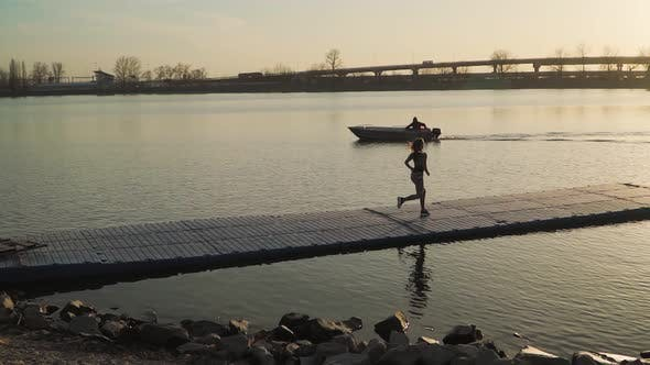 An Athletic Girl Running on the Pier Along the Lake on the Background of a Beautiful Sunset.