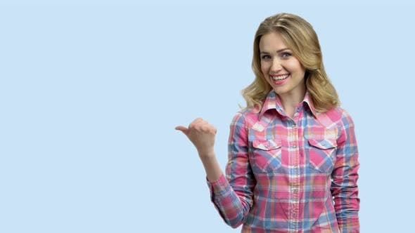 Smiling Woman Pointing Thumb Behind Her Back