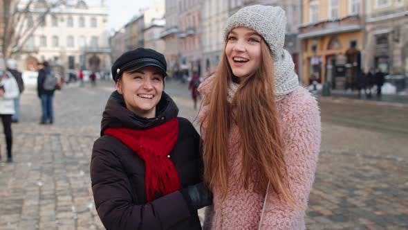 Two Smiling Women Tourists Walking Together on City Street Family Couple Talking Embracing