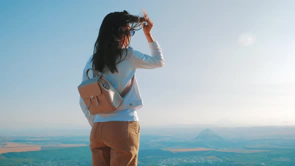 Young Woman with Backpack Standing on Cliff and Looking To a Sky