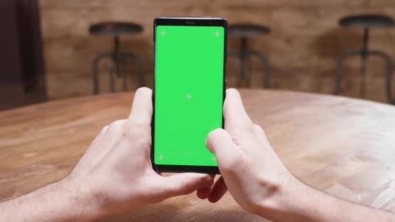 Static Shot of Male Hands Holding a Phone with Green Screen Display