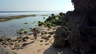 Woman Walks in the Beach Near to Rocks Seaweed