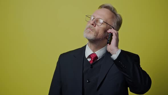 Thumbnail for Serious elderly man talking the mobile phone