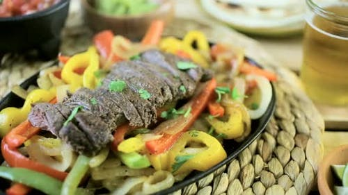 Outdoor cooking. Steak fajitas with bell peppers and yellow onion on a cast iron fajita skillet.