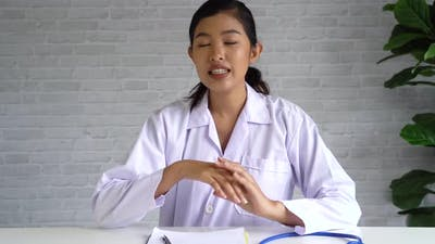 Camera View of Online Video Conference Chat with Asian Female Doctor and Patient Looking at Camera
