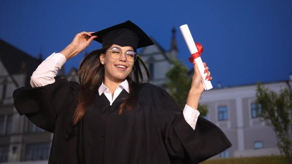 Thumbnail for Happy graduating female student dancing.