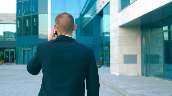 Thumbnail for Young Businessman Talking on Phone and Walking in Street. Unrecognizable Man Having Business
