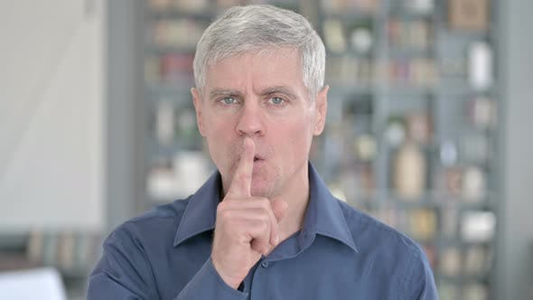 Portrait of Middle Aged Man Asking To Be Quiet By Putting Finger on Lips