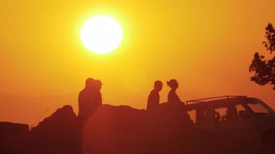 People walking outdoor against golden sunset