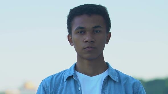 Pensive African-American teenager boy touching chin