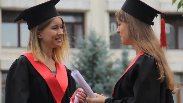 Thumbnail for Graduates in Academic Dresses Holding Diplomas and Talking After Graduation