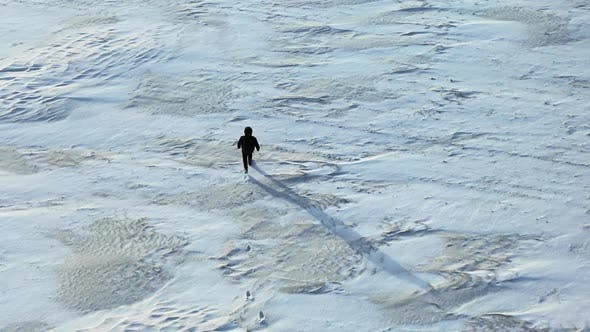 Thumbnail for Aerial View: Camera Following the Man, Who Crossing the Snow Desert