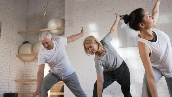 Thumbnail for Mature Man and Woman Doing Yoga with Teacher in Studio