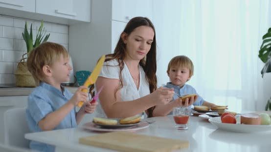 Thumbnail for A Happy Family Is a Young Beautiful Mother in a White Dress with Two Sons in Blue Shirts Preparing a