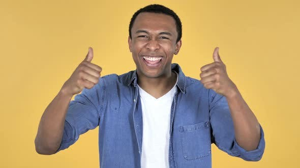 Thumbnail for Young African Man Gesturing Thumbs Up, Yellow Background