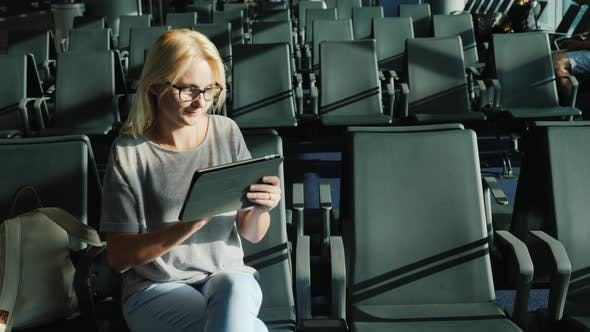 Thumbnail for A Woman Sits Alone Among the Rows of Empty Chairs in the Waiting Room. Uses a Tablet