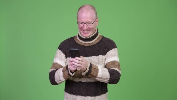 Thumbnail for Happy Mature Bald Man with Turtleneck Sweater Using Phone