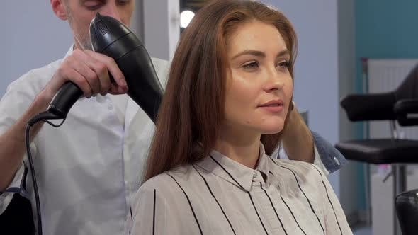 Gorgeous Woman Smiling To the Camera While Getting Her Hair Blow Dried