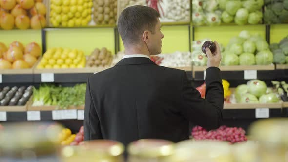 Thumbnail for Back View of Brunette Young Caucasian Man Smelling Red Onion in Grocery. Rear View of Adult Guy in