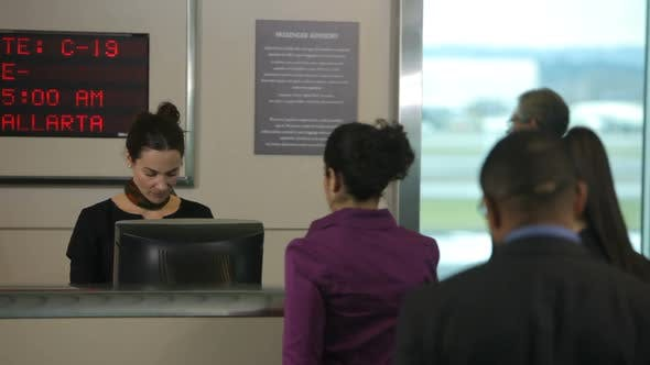 Thumbnail for Airport passengers check in at ticket counter