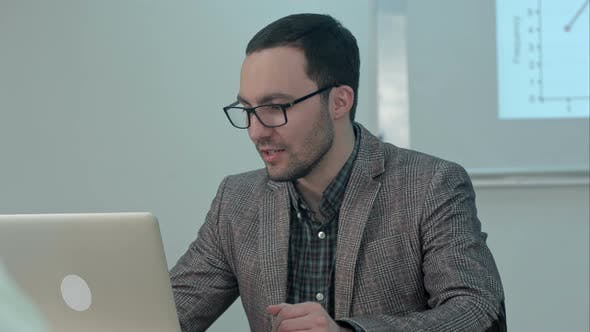 Thumbnail for Positive Male Teacher Typing on a Laptop Sitting at a Table and Talk To Class