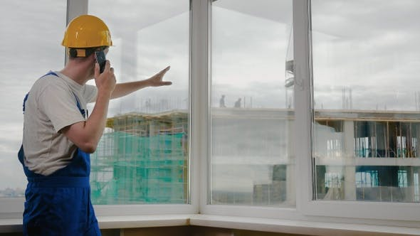 Cover Image for Builder at construction site calling his collegues to give