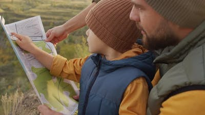 Parents and Child Looking at Map on Hike