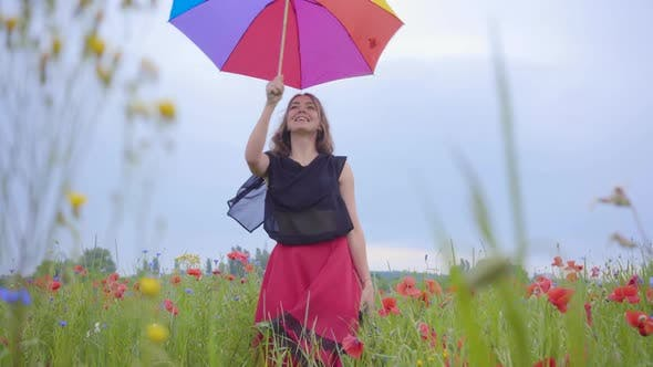 Thumbnail for Adorable Young Girl Under Colorful Umbrella Dancing in a Poppy Field Smiling Happily Looking