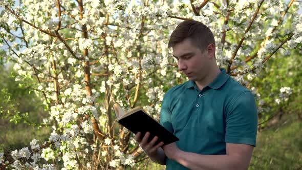Thumbnail for Young Man on Nature with a Book in His Hands. A Man Reads a Book While Standing Against a Flowering