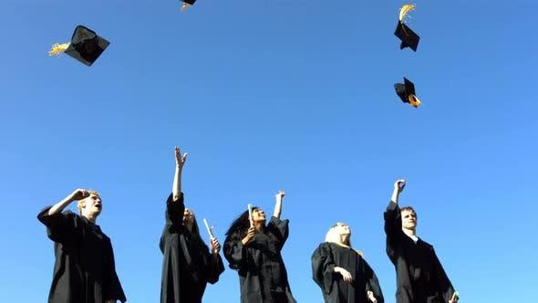 Thumbnail for Gruppe von Absolventen werfen Graduierung Kappen