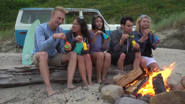 Thumbnail for Group of friends at beach hanging out by campfire blowing bubbles
