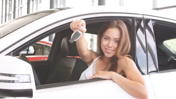 Thumbnail for Happy Overjoyed Brunette Female New Car Owner Sitting in White Car and Demonstrates the Key