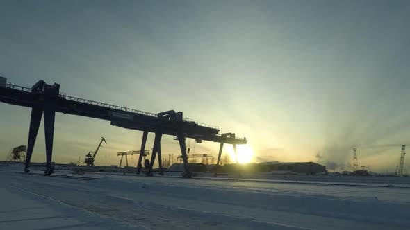 Gantry Crane In The Industrial Zone In Winter Morning On Rising Sun Background
