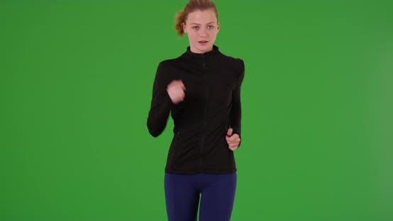Young white girl in sportswear running toward the camera on green screen