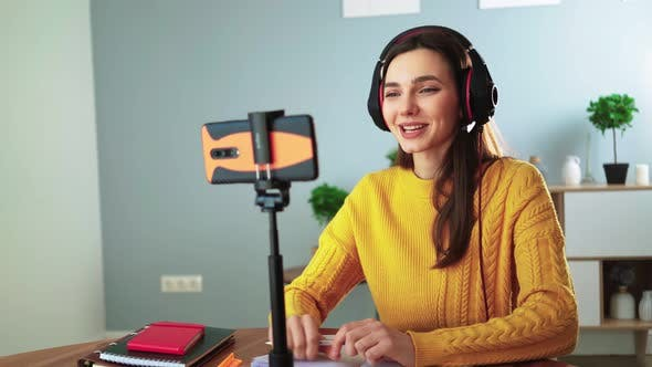 Happy Young Teacher in Headphones Communicates By Video Call Using Mobile Phone