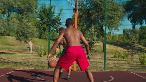 Sportsman Dribbling Ball at Outdoor Urban Court