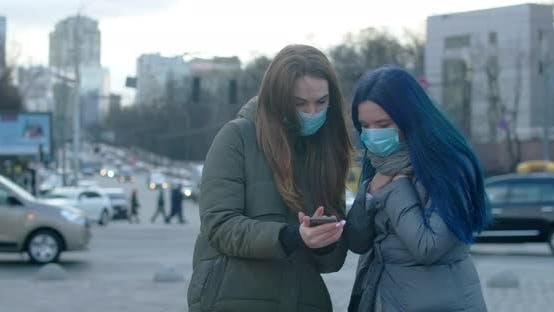 Thumbnail for Young Women in Protective Masks Using Smartphone. Brunette Girl Moving Aside As Her Friend Coughing